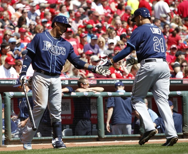 Apr 12, 2014; Cincinnati, OH, USA; Tampa Bay Rays first baseman James Loney (21) celebrates with shortstop Yunel Escobar (11) after hitting a home run during the second inning against the Cincinnati Reds at Great American Ball Park. Mandatory Credit: Frank Victores-USA TODAY Sports