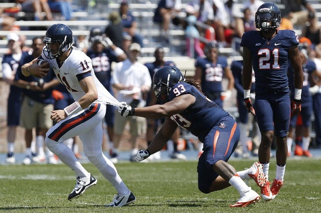 Apr 12, 2014; Charlottesville, VA, USA; Virginia Cavaliers quarterback Greyson Lambert (11) is tackled by defensive tackle Donte Wilkins (93) while running with the ball during the Cavaliers Spring Game at Scott Stadium. Mandatory Credit: Geoff Burke-USA TODAY Sports