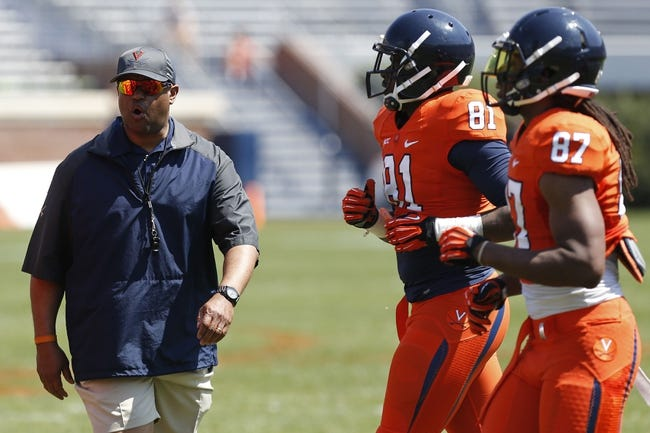 Apr 12, 2014; Charlottesville, VA, USA; Virginia Cavaliers head coach Mike London (left) talks to his team on the field during the Cavaliers Spring Game at Scott Stadium. Mandatory Credit: Geoff Burke-USA TODAY Sports