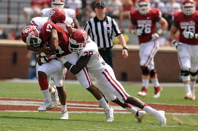 Apr 12, 2014; Norman, OK, USA; Oklahoma Sooners wide receiver Jordan Smallwood (17) is tackled by Sooners linebacker Aaron Franklin (25) and Sooners safetyDarius Owens (39) at Gaylord Family Oklahoma Memorial Stadium. Mandatory Credit: Mark D. Smith-USA TODAY Sports