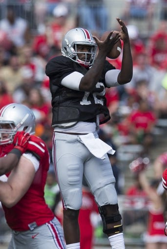 Apr 12, 2014; Columbus, OH, USA; Ohio State scarlet team quarterback Cardale Jones (12) recovers a loose ball during the Ohio State Buckeyes spring game at Ohio Stadium. The scarlet team won the game 17-7. Mandatory Credit: Greg Bartram-USA TODAY Sports