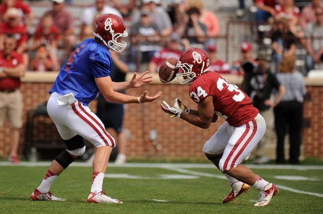 Apr 12, 2014; Norman, OK, USA; Oklahoma Sooners quarterback Justice Hansen (4) bobbles the ball while attempting a handoff to Sooners running back Daniel Brooks (34) during the spring game at Gaylord Family Oklahoma Memorial Stadium. Mandatory Credit: Mark D. Smith-USA TODAY Sports