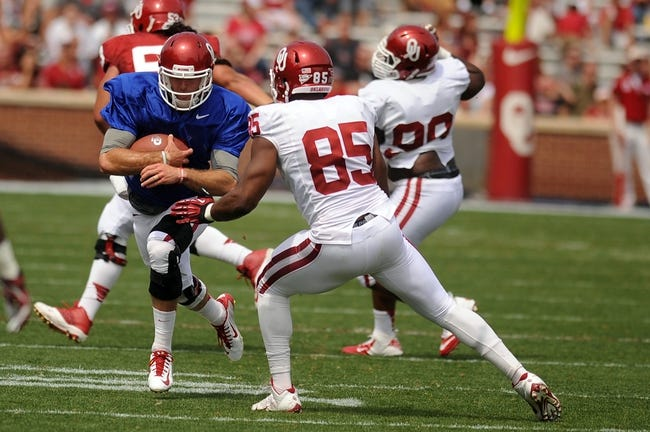 Apr 12, 2014; Norman, OK, USA;  Oklahoma Sooners quarterback Trevor Knight (9) runs the ball in front of Sooners defensive end Geneo Grissom (85) during the spring game at Gaylord Family Oklahoma Memorial Stadium. Mandatory Credit: Mark D. Smith-USA TODAY Sports