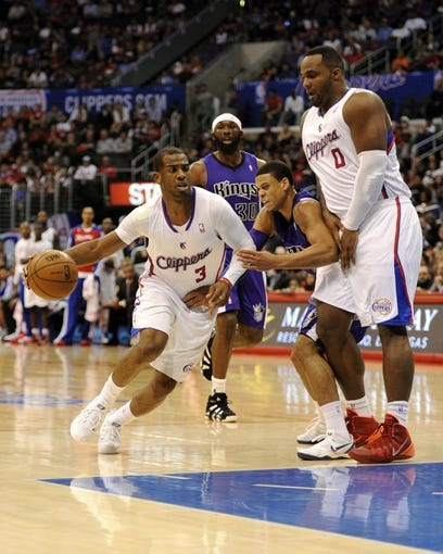 Apr 12, 2014; Los Angeles, CA, USA; Los Angeles Clippers guard Chris Paul (3) moves the ball around a pick from Los Angeles Clippers forward Glen Davis (0) defended by Sacramento Kings guard Ray McCallum (center) during the third quarter at Staples Center. The Los Angeles Clippers won 117-101. Mandatory Credit: Kelvin Kuo-USA TODAY Sports