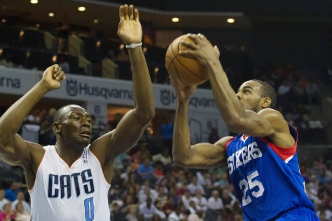 Apr 12, 2014; Charlotte, NC, USA; Philadelphia 76ers guard Elliot Williams (25) goes up for a shot while Charlotte Bobcats center Bismack Biyombo (0) defends during the first half at Time Warner Cable Arena. Mandatory Credit: Jeremy Brevard-USA TODAY Sports