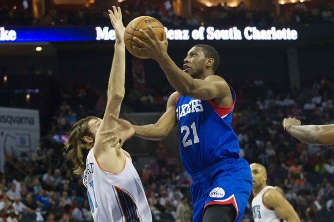 Apr 12, 2014; Charlotte, NC, USA; Philadelphia 76ers forward Thaddeus Young (21) shoots the ball over Charlotte Bobcats forward Josh McRoberts (11) during the first half at Time Warner Cable Arena. Mandatory Credit: Jeremy Brevard-USA TODAY Sports