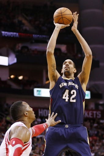 Apr 12, 2014; Houston, TX, USA; New Orleans Pelicans center Alexis Ajinca (42) shoots the ball over Houston Rockets center Dwight Howard (front) during the first half at Toyota Center. Mandatory Credit: Soobum Im-USA TODAY Sports