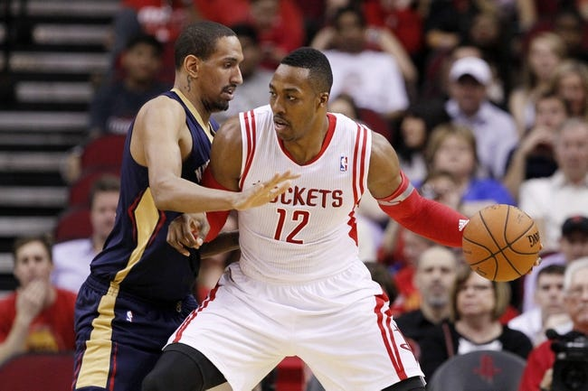 Apr 12, 2014; Houston, TX, USA; Houston Rockets center Dwight Howard (12) drives against New Orleans Pelicans center Alexis Ajinca (left) during the first half at Toyota Center. Mandatory Credit: Soobum Im-USA TODAY Sports