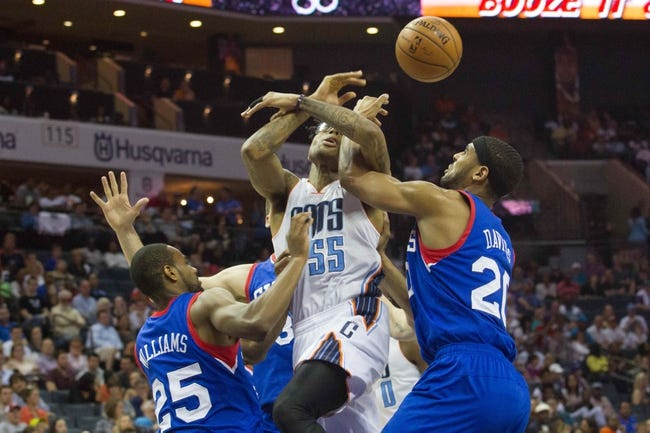 Apr 12, 2014; Charlotte, NC, USA; Charlotte Bobcats guard Chris Douglas-Roberts (55) gets fouled by Philadelphia 76ers forward Brandon Davies (20) during the second half at Time Warner Cable Arena. The Bobcats defeated the 76ers 111-105. Mandatory Credit: Jeremy Brevard-USA TODAY Sports