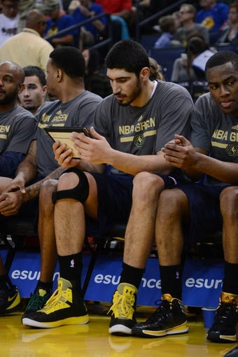 Apr 6, 2014; Oakland, CA, USA; Utah Jazz center Enes Kanter (0) looks at an iPad during the third quarter against the Golden State Warriors at Oracle Arena. The Warriors defeated the Jazz 130-102. Mandatory Credit: Kyle Terada-USA TODAY Sports