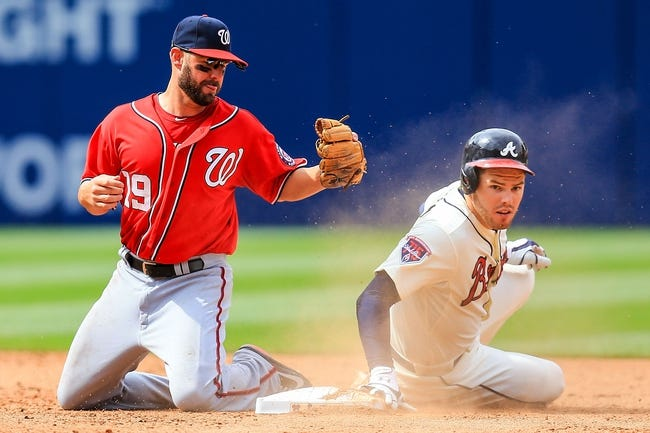 Apr 13, 2014; Atlanta, GA, USA; Atlanta Braves first baseman Freddie Freeman (5) slides into second with a double on a missed catch by Washington Nationals first baseman Kevin Frandsen (19 in the eighth inning at Turner Field. Mandatory Credit: Daniel Shirey-USA TODAY Sports