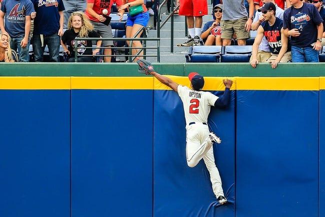 Apr 13, 2014; Atlanta, GA, USA; Atlanta Braves center fielder B.J. Upton (2) climbs the wall in an attempt to catch a Washington Nationals first baseman Adam LaRoche (25) home run in the ninth inning at Turner Field. The Braves won 10-2. Mandatory Credit: Daniel Shirey-USA TODAY Sports