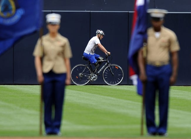 Apr 13, 2014; San Diego, CA, USA; USMC veteran Rob Jones rides along the warning track prior to throwing out the honorary first pitch on military opening day before the San Diego Padres game against the Detroit Tigers at Petco Park. Jones biked from Maine to San Diego as a part of Ride 2 Recovery for healing heroes. Mandatory Credit: Christopher Hanewinckel-USA TODAY Sports