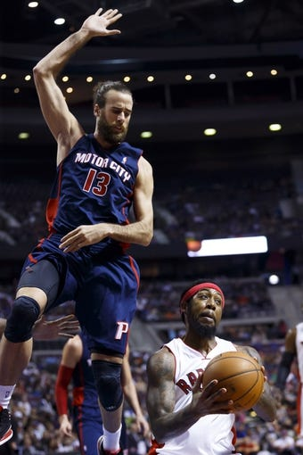 Apr 13, 2014; Auburn Hills, MI, USA; Detroit Pistons forward Luigi Datome (13) leaps in the air on Toronto Raptors forward John Salmons (25) in the second quarter at The Palace of Auburn Hills. Mandatory Credit: Rick Osentoski-USA TODAY Sports