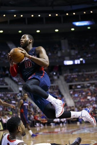 Apr 13, 2014; Auburn Hills, MI, USA; Detroit Pistons forward Greg Monroe (10) moves the ball on Toronto Raptors forward Amir Johnson (15) in the third quarter at The Palace of Auburn Hills. Toronto won 116-107. Mandatory Credit: Rick Osentoski-USA TODAY Sports
