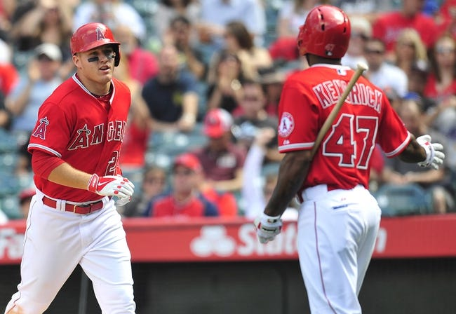 April 13, 2014; Anaheim, CA, USA; Los Angeles Angels center fielder Mike Trout (27) is congratulated by second baseman Howie Kendrick (47) after scoring a run in the sixth inning against the New York Mets at Angel Stadium of Anaheim. Mandatory Credit: Gary A. Vasquez-USA TODAY Sports
