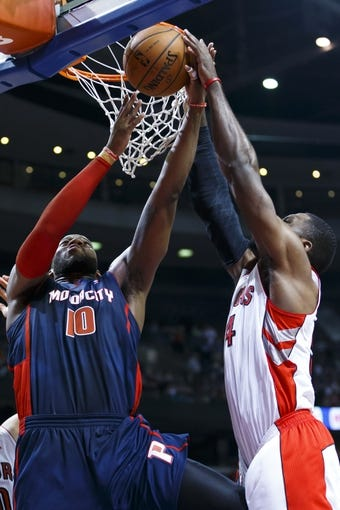 Apr 13, 2014; Auburn Hills, MI, USA; Detroit Pistons forward Greg Monroe (10) tries to shoot on Toronto Raptors forward Patrick Patterson (54) in the fourth quarter at The Palace of Auburn Hills. Mandatory Credit: Rick Osentoski-USA TODAY Sports