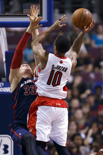 Apr 13, 2014; Auburn Hills, MI, USA; Toronto Raptors guar atDeMar DeRozan (10) shoots on Detroit Pistons forward Jonas Jerebko (33) in the fourth quarter at The Palace of Auburn Hills. Toronto won 116-107. Mandatory Credit: Rick Osentoski-USA TODAY Sports