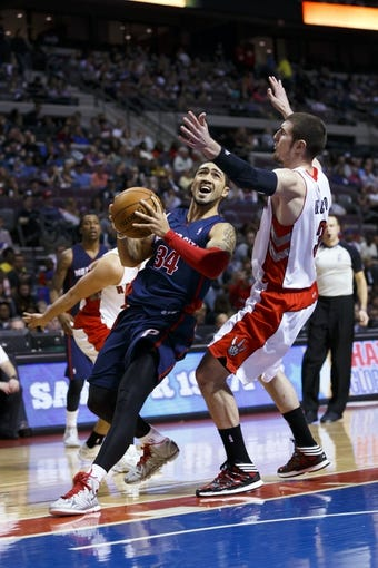 Apr 13, 2014; Auburn Hills, MI, USA; Detroit Pistons guard Peyton Siva (34) dribbles around Toronto Raptors guard Nando de Colo (3) in the fourth quarter at The Palace of Auburn Hills. Toronto won 116-107. Mandatory Credit: Rick Osentoski-USA TODAY Sports