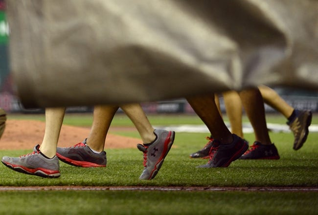 Apr 13, 2014; St. Louis, MO, USA; The St. Louis Cardinals grounds crew carries the tarp on the field during a rain delay in the third inning against the Chicago Cubs at Busch Stadium. Mandatory Credit: Scott Rovak-USA TODAY Sports