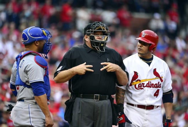 Apr 13, 2014; St. Louis, MO, USA; Chicago Cubs catcher Welington Castillo (5) and St. Louis Cardinals catcher Yadier Molina (4) look on as umpire Jerry Layne (24) attempts to figure out what the count is at Busch Stadium. The Cardinals defeated the Cubs 6-4. Mandatory Credit: Scott Rovak-USA TODAY Sports