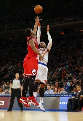 Apr 13, 2014; New York, NY, USA;  New York Knicks forward Carmelo Anthony (7) gets off a jump shot against Chicago Bulls forward Taj Gibson (22) during the second half at Madison Square Garden. New York Knicks defeat the Chicago Bulls 100-89. Mandatory Credit: Jim O'Connor-USA TODAY Sports