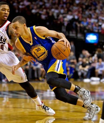 Apr 13, 2014; Portland, OR, USA; Golden State Warriors guard Stephen Curry (30) drives around Portland Trail Blazers guard Damian Lillard (0) during the fourth quarter at the Moda Center. Mandatory Credit: Craig Mitchelldyer-USA TODAY Sports