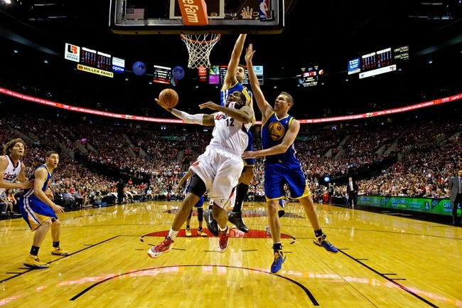 Apr 13, 2014; Portland, OR, USA; Portland Trail Blazers forward LaMarcus Aldridge (12) is fouled by Golden State Warriors center Andrew Bogut (12) and forward David Lee (10) during the fourth quarter at the Moda Center. Mandatory Credit: Craig Mitchelldyer-USA TODAY Sports