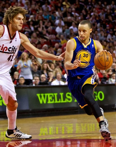 Apr 13, 2014; Portland, OR, USA; Golden State Warriors guard Stephen Curry (30) drives past Portland Trail Blazers center Robin Lopez (42) during overtime at the Moda Center. Mandatory Credit: Craig Mitchelldyer-USA TODAY Sports