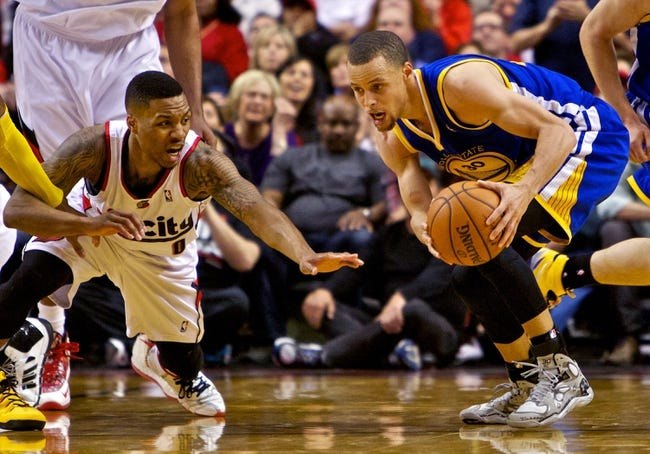 Apr 13, 2014; Portland, OR, USA; Portland Trail Blazers guard Damian Lillard (0) and Golden State Warriors guard Stephen Curry (30) dive for a loose ball during overtime at the Moda Center. Mandatory Credit: Craig Mitchelldyer-USA TODAY Sports