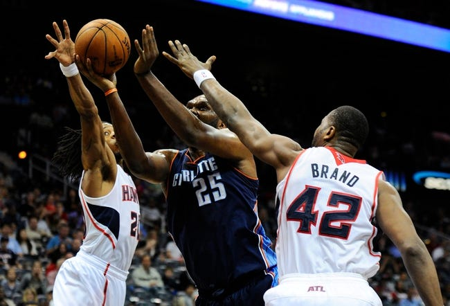 Apr 14, 2014; Atlanta, GA, USA; Charlotte Bobcats center Al Jefferson (25) controls the ball between Atlanta Hawks  forward Cartier Martin (20) and forward Elton Brand (42) during the first half at Philips Arena. Mandatory Credit: Dale Zanine-USA TODAY Sports