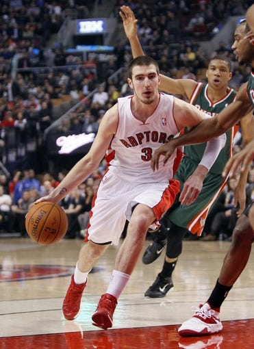 Apr 14, 2014; Toronto, Ontario, CAN; Toronto Raptors guard Nando De Colo (3) carries the ball against the Milwaukee Bucks during the first half at the Air Canada Centre. Mandatory Credit: John E. Sokolowski-USA TODAY Sports