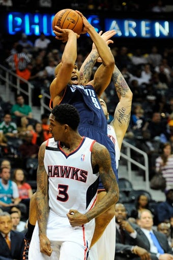 Apr 14, 2014; Atlanta, GA, USA; Charlotte Bobcats guard Gerald Henderson (9) shoots at the basket between Atlanta Hawks center Pero Antic (6) and guard Louis Williams (3) during the first half at Philips Arena. Mandatory Credit: Dale Zanine-USA TODAY Sports