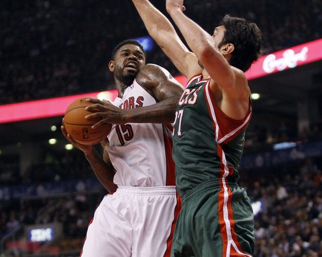Apr 14, 2014; Toronto, Ontario, CAN; Toronto Raptors forward-center Amir Johnson (15) goes to shoot as Milwaukee Bucks center Zaza Pachulia (27) defends during the first half at the Air Canada Centre. Mandatory Credit: John E. Sokolowski-USA TODAY Sports