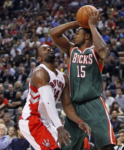 Apr 14, 2014; Toronto, Ontario, CAN; Toronto Raptors forward Patrick Patterson (54) defends against Milwaukee Bucks forward Chris Wright (15) at the Air Canada Centre. Toronto defeated Milwaukee 110-100. Mandatory Credit: John E. Sokolowski-USA TODAY Sports