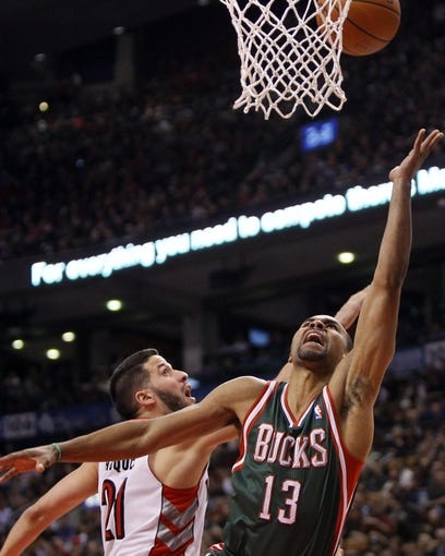Apr 14, 2014; Toronto, Ontario, CAN; Milwaukee Bucks guard Ramon Sessions (13) goes to make a basket as Toronto Raptors guard Greivis Vasquez (21)  defends at the Air Canada Centre. Toronto defeated Milwaukee 110-100. Mandatory Credit: John E. Sokolowski-USA TODAY Sports