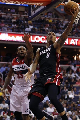 Apr 14, 2014; Washington, DC, USA; Miami Heat forward Michael Beasley (8) shoots the ball as Washington Wizards forward Trevor Booker (35) defends in the fourth quarter at Verizon Center. The Wizards won 114-93. Mandatory Credit: Geoff Burke-USA TODAY Sports