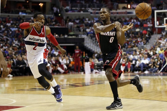 Apr 14, 2014; Washington, DC, USA; Miami Heat guard Toney Douglas (0) passes the ball as Washington Wizards guard John Wall (2) defends in the fourth quarter at Verizon Center. The Wizards won 114-93. Mandatory Credit: Geoff Burke-USA TODAY Sports