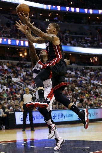 Apr 14, 2014; Washington, DC, USA; Miami Heat forward Michael Beasley (8) shoots the ball as Washington Wizards forward Al Harrington (7) defends in the fourth quarter at Verizon Center. The Wizards won 114-93. Mandatory Credit: Geoff Burke-USA TODAY Sports