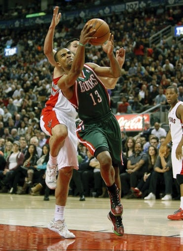 Apr 14, 2014; Toronto, Ontario, CAN; Milwaukee Bucks guard Ramon Sessions (13) goes to the net against Toronto Raptors guard Greivis Vasquez (21) at the Air Canada Centre. Toronto defeated Milwaukee 110-100. Mandatory Credit: John E. Sokolowski-USA TODAY Sports
