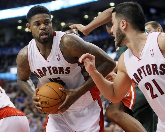 Apr 14, 2014; Toronto, Ontario, CAN; Toronto Raptors forward-center Amir Johnson (15) looks to pass to guard Greivis Vasquez (21) against the Milwaukee Bucks at the Air Canada Centre. Toronto defeated Milwaukee 110-100. Mandatory Credit: John E. Sokolowski-USA TODAY Sports
