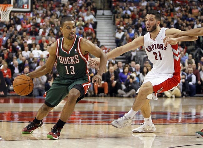 Apr 14, 2014; Toronto, Ontario, CAN; Milwaukee Bucks guard Ramon Sessions (13) tries to get by Toronto Raptors guard Greivis Vasquez (21) at the Air Canada Centre. Toronto defeated Milwaukee 110-100. Mandatory Credit: John E. Sokolowski-USA TODAY Sports
