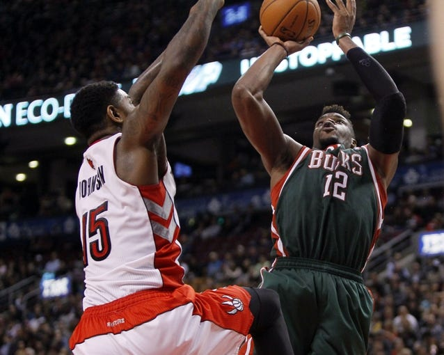 Apr 14, 2014; Toronto, Ontario, CAN; Toronto Raptors forward-center Amir Johnson (15) defends against Milwaukee Bucks forward Jeff Adrien (12) at the Air Canada Centre. Toronto defeated Milwaukee 110-100. Mandatory Credit: John E. Sokolowski-USA TODAY Sports