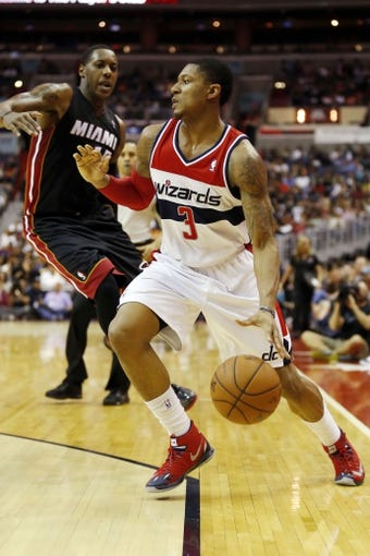 Apr 14, 2014; Washington, DC, USA; Washington Wizards guard Bradley Beal (3) dribbles the ball as Miami Heat guard Mario Chalmers (15) defends in the second quarter at Verizon Center. The Wizards won 114-93. Mandatory Credit: Geoff Burke-USA TODAY Sports