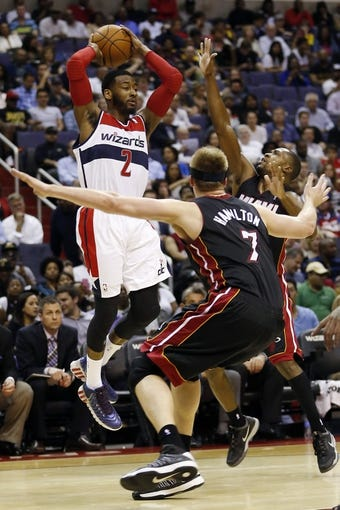 Apr 14, 2014; Washington, DC, USA; Washington Wizards guard John Wall (2) leaps to pass the ball as Miami Heat center Justin Hamilton (7) and Heat forward Michael Beasley (8) defend in the second quarter at Verizon Center. The Wizards won 114-93. Mandatory Credit: Geoff Burke-USA TODAY Sports