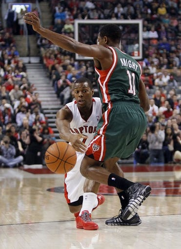 Apr 14, 2014; Toronto, Ontario, CAN; Toronto Raptors guard Kyle Lowry (7) passes the ball past Milwaukee Bucks guard Brandon Knight (11) at the Air Canada Centre. Toronto defeated Milwaukee 110-100. Mandatory Credit: John E. Sokolowski-USA TODAY Sports