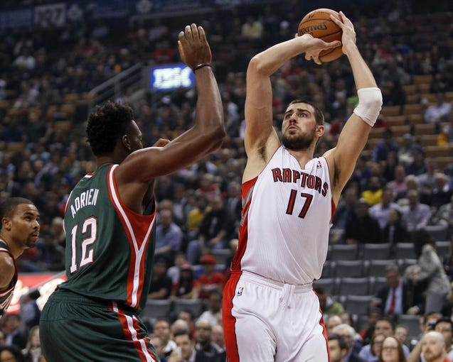 Apr 14, 2014; Toronto, Ontario, CAN; Toronto Raptors center Jonas Valanciunas (17) goes to shoot as Milwaukee Bucks forward Jeff Adrien (12) defends at the Air Canada Centre. Toronto defeated Milwaukee 110-100. Mandatory Credit: John E. Sokolowski-USA TODAY Sports