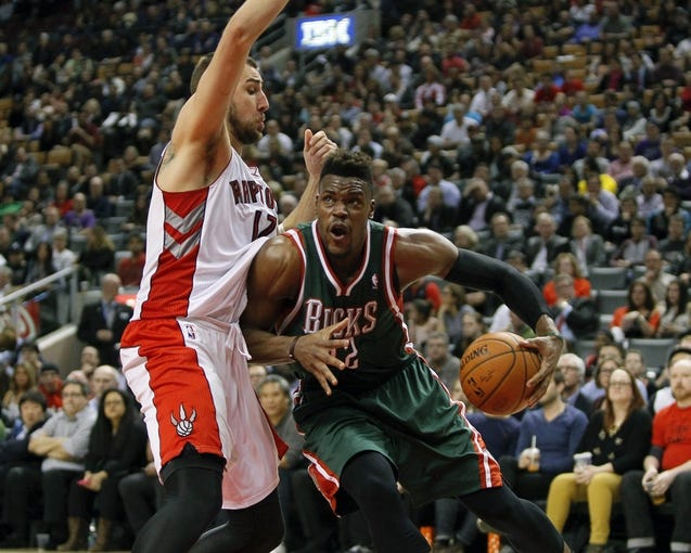 Apr 14, 2014; Toronto, Ontario, CAN; Milwaukee Bucks forward Jeff Adrien (12) drives to the net against Toronto Raptors center Jonas Valanciunas (17) at the Air Canada Centre. Toronto defeated Milwaukee 110-100. Mandatory Credit: John E. Sokolowski-USA TODAY Sports