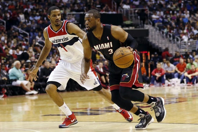 Apr 14, 2014; Washington, DC, USA; Miami Heat guard Dwyane Wade (3) dribbles the ball as Washington Wizards forward Trevor Ariza (1) defends in the third quarter at Verizon Center. The Wizards won 114-93. Mandatory Credit: Geoff Burke-USA TODAY Sports