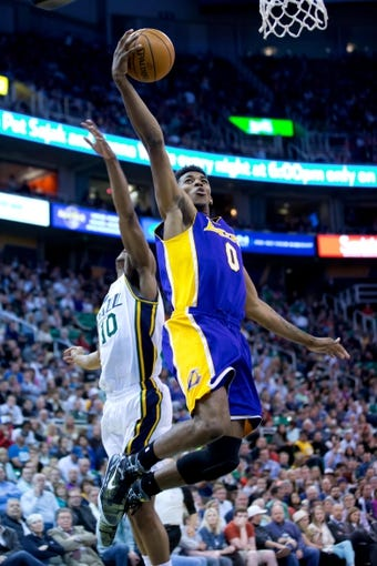 Apr 14, 2014; Salt Lake City, UT, USA; Los Angeles Lakers forward Nick Young (0) goes to the basket in front of Utah Jazz guard Alec Burks (10) during the first half at EnergySolutions Arena. Mandatory Credit: Russ Isabella-USA TODAY Sports